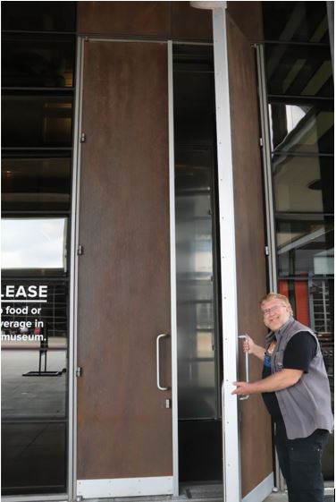 Gary opening a huge door at the Harley Davidson Museum