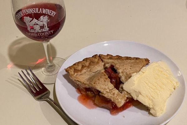 A slice of strawberry rhubarb pie with ice cream